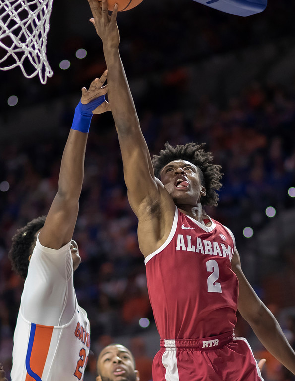 . Alabama guard Collin Sexton (2) shoots a layup over Florida forward Dontay Bassett (21) during the first half of an NCAA college basketball game in Gainesville, Fla., Saturday, Feb. 3, 2018. Alabama won 68-50. (AP Photo/Ron Irby)