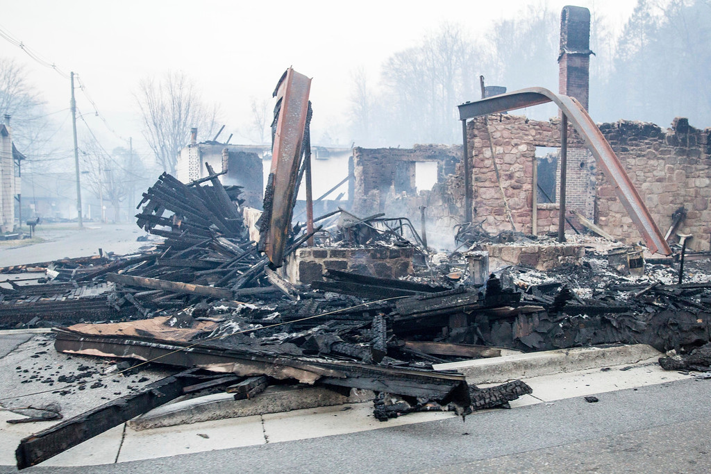 . A burned out building smolders in Gatlinburg, Tenn., Tuesday, Nov. 29, 2016. The fatal wildfires swept over the tourist town the night before, causing widespread damage. (AP Photo/Erik Schelzig)
