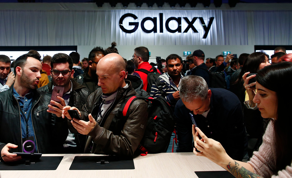 . People attend the reveal of the new the Galaxy S9 of the Samsung Galaxy Unpacked 2018 event on the eve of the Mobile World Congress wireless show, in Barcelona, Spain, Sunday, Feb. 25, 2018. Samsung unveiled new smartphones with largely unchanged designs and incremental improvements such as a better camera. (AP Photo/Manu Fernandez)