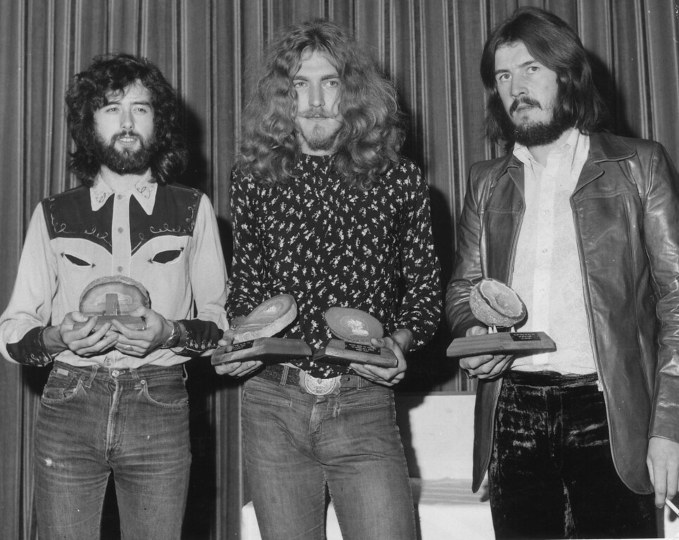 . 16th September 1970:  British rock band Led Zeppelin collect their geode awards after being voted top British group in the Melody Maker Pop Poll in London. From left to right, they are Jimmy Page, Robert Plant (who also won the Best British Singer award), and John Bonham.  (Photo by Roger Jackson/Central Press/Getty Images)