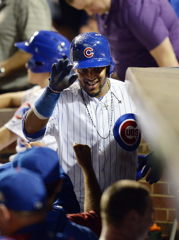 . Emilio Bonifacio #64 of the Chicago Cubs is greeted at the dugout after hitting a two-run home run, scoring Nate Schierholtz during the fourth inning against the Colorado Rockies on July 29, 2014 at Wrigley Field in Chicago, Illinois.  (Photo by Brian Kersey/Getty Images)