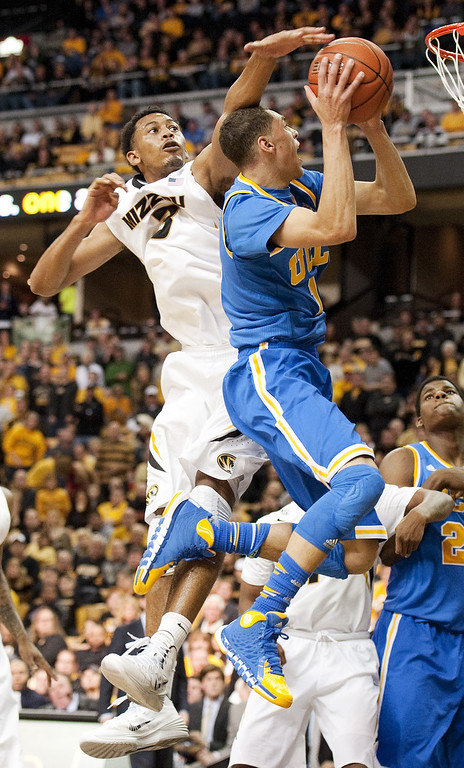 . Missouri\'s Johnathan Williams III, left, tries to block the shot of UCLA\'s Zach LaVine, right, as he shoots during the second half of an NCAA college basketball  game Saturday, Dec. 7, 2013, in Columbia, Mo. Missouri won the game 80-71. (AP Photo/L.G. Patterson)