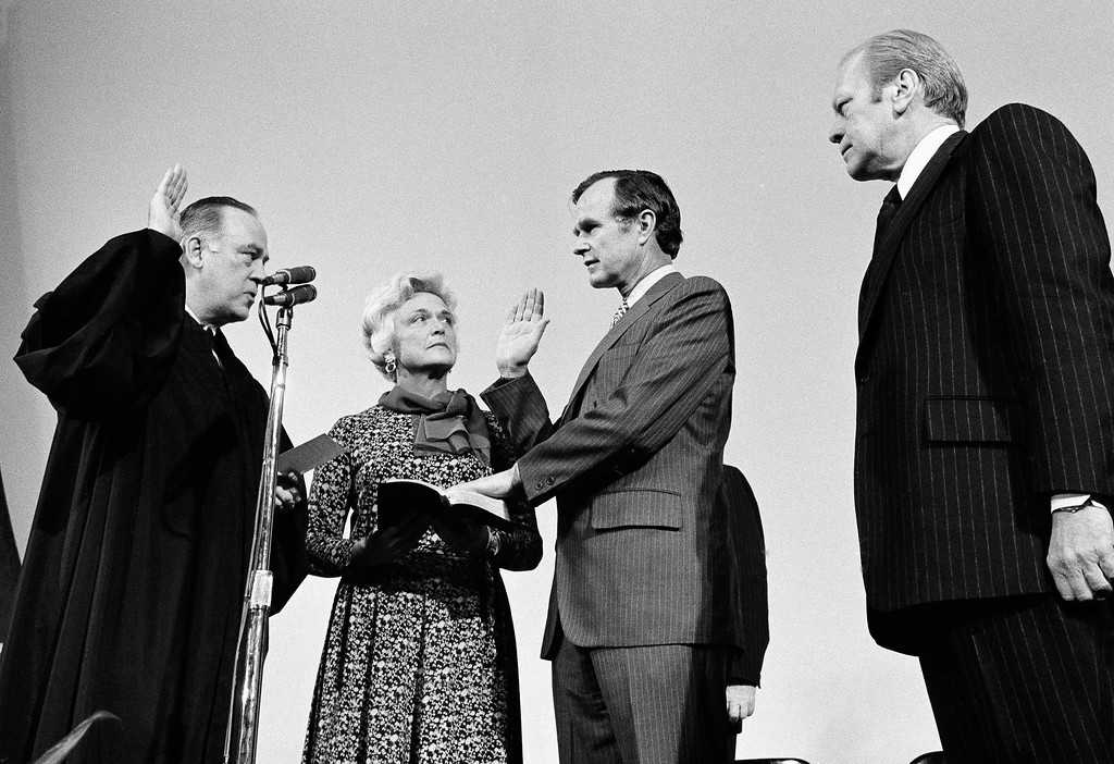 . George Bush is sworn in as new director of the Central Intelligence Agency by Supreme Court Associate Justice Potter Stewart, left, as Mrs Barbara Bush and President Gerald Ford, at right, look on at CIA headquarters in Langley, Va., January 30, 1976.     Bush succeeds William Colby who retired. (AP Photo)