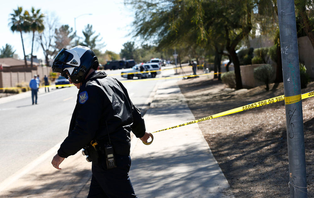 Description of . A Phoenix Police Department officer, puts up police tape near a home of a suspected gunman who opened fire at a Phoenix office building on Wednesday wounding three people, one of them critically, and setting off a manhunt that led police to surround his house for several hours before they discovered he wasn't there Jan. 30, 2013, in Phoenix. Authorities believe there was only one shooter, but have not identified him or a possible motive for the shooting. They don't believe the midmorning shooting at the complex was a random act. (AP Photo/Ross D. Franklin)