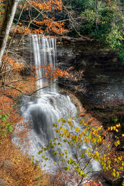 Beautiful tall waterfall viewed through colorful autumn leaves.