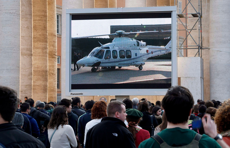 """. People in Saint Peter\'s Square in the Vatican City watch a giant screen of the helicopter waiting to carry Pope Benedict XVI  to the papal summer residence at Castelgandolfo, February 28, 2013. Pope Benedict slips quietly from the world stage on Thursday after a private last goodbye to his cardinals and a short flight to a country palace to enter the final phase of his life \""""hidden from the world\"""".           REUTERS/Stefano Rellandini"""
