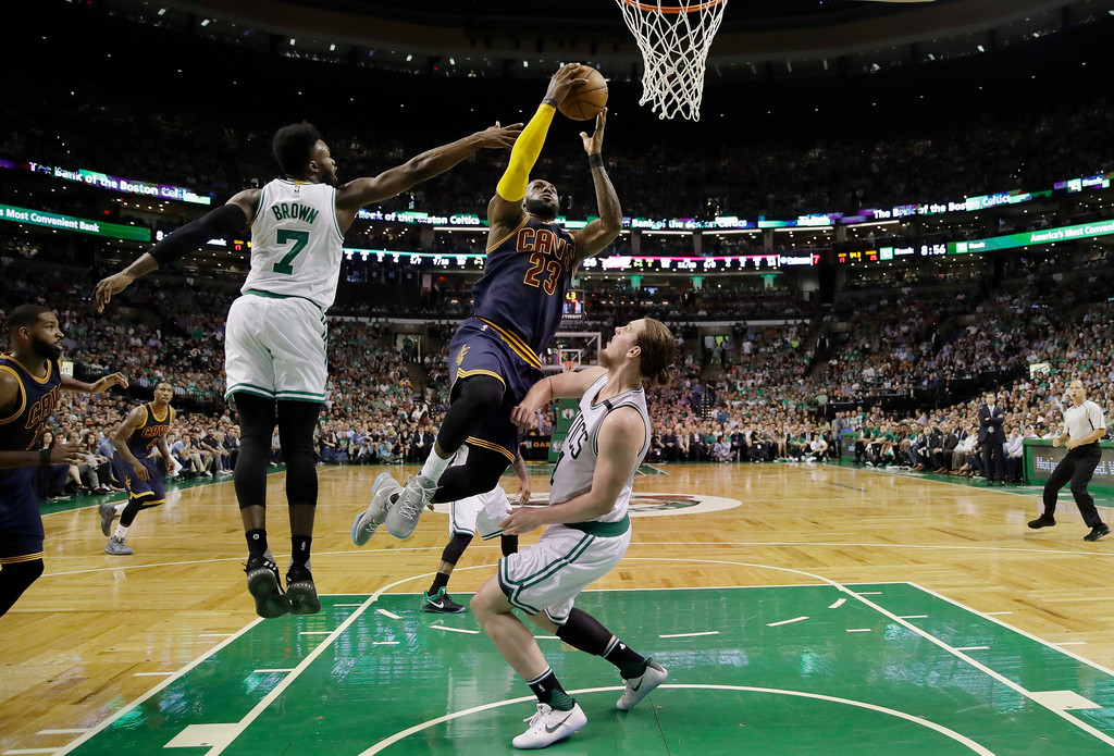 . Cleveland Cavaliers forward LeBron James (23) drives between Boston Celtics forward Jaylen Brown, left, and center Kelly Olynyk during the first quarter of Game 1 of the NBA basketball Eastern Conference finals, Wednesday, May 17, 2017, in Boston. (AP Photo/Charles Krupa)