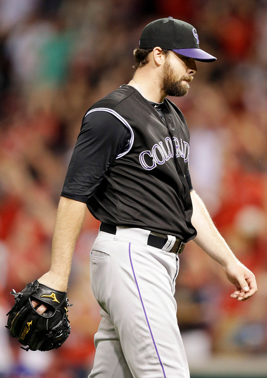. Colorado Rockies relief pitcher Boone Logan walks off the field after giving up a walkoff solo home run to Cincinnati Reds\' Joey Votto in the ninth inning of a baseball game on Friday, May 9, 2014, in Cincinnati. Cincinnati won 4-3. (AP Photo/Al Behrman)