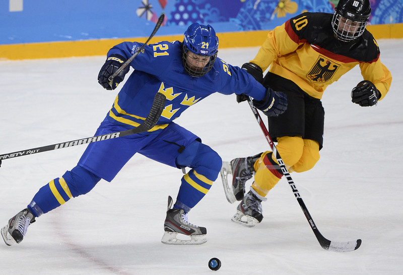 . Sweden\'s Erica Uden Johansson (L) vies with Germany\'s Anja Weisser during the Women\'s Ice Hockey Group B match Germany vs Sweden at the Shayba Arena during the Sochi Winter Olympics on February 11, 2014.  (JONATHAN NACKSTRAND/AFP/Getty Images)