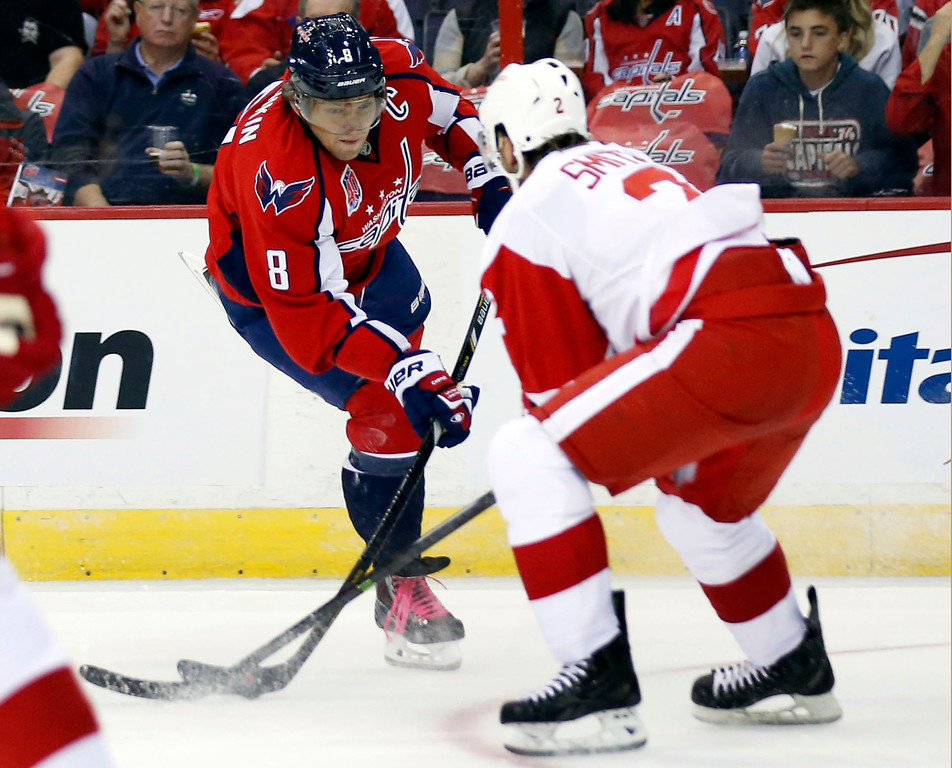 . Washington Capitals left wing Alex Ovechkin (8), from Russia, attempts to shoot past Detroit Red Wings defenseman Brendan Smith (2) in the first period of an NHL hockey game, Wednesday, Oct. 29, 2014, in Washington. (AP Photo/Alex Brandon)