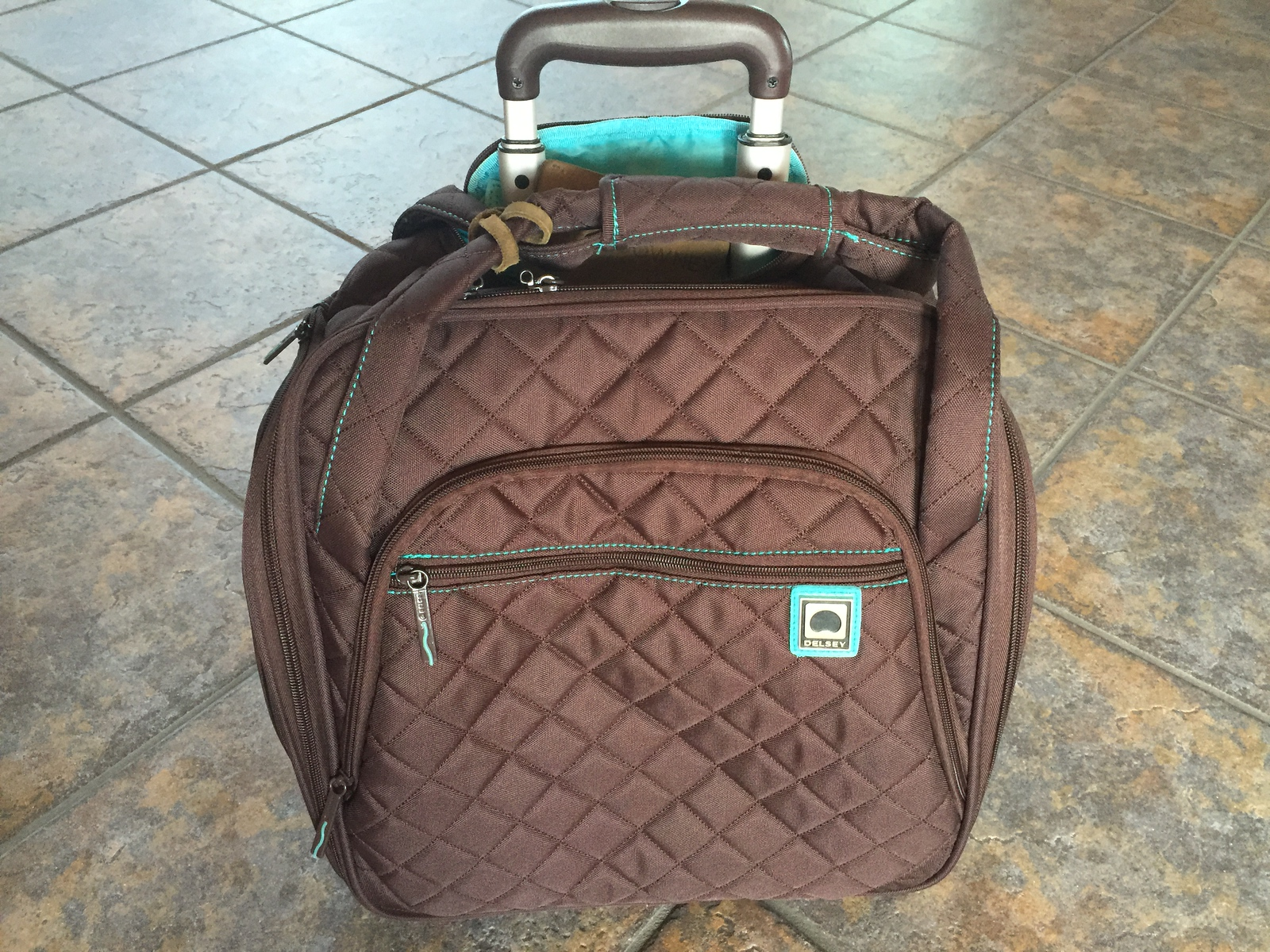 This quilted Delsey rolling tote bag fits underneath most airline seats. It's one of our travel favorites.