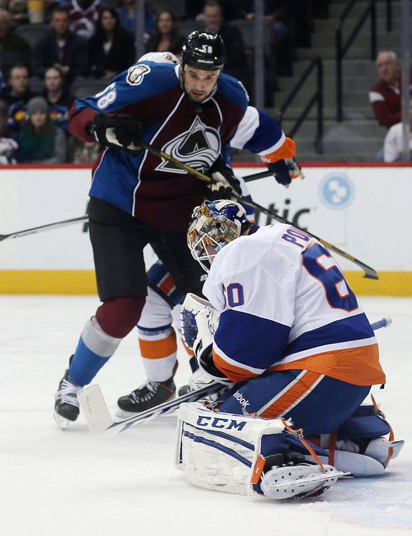 . New York Islanders goalie Kevin Poulin, front, makes glove save of a redirected shot off the stick of Colorado Avalanche left wing Patrick Bordeleau during the first period of an NHL hockey game in Denver on Friday, Jan. 10, 2014. (AP Photo/David Zalubowski)