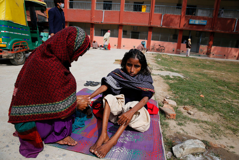 . In this Monday, Feb. 3, 2014 photo, a tuberculosis patient Neha, 11, sits in the sun with her mother Jehana outside Lal Bahadur Shastri Government Hospital at Ram Nagar in Varanasi, India. (AP Photo/Rajesh Kumar Singh)