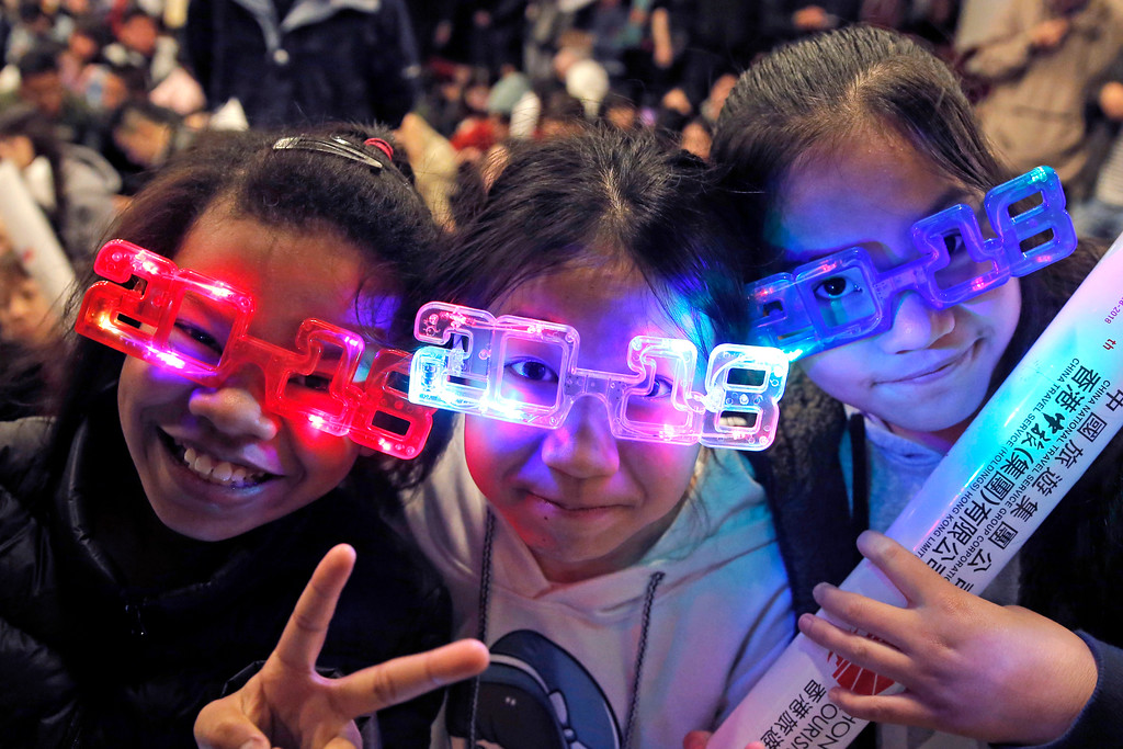. Residents wear 2018 glasses, during New Year\'s Eve to celebrate the upcoming year 2018 in Hong Kong, Sunday, Dec. 31, 2017. (AP Photo/Kin Cheung)