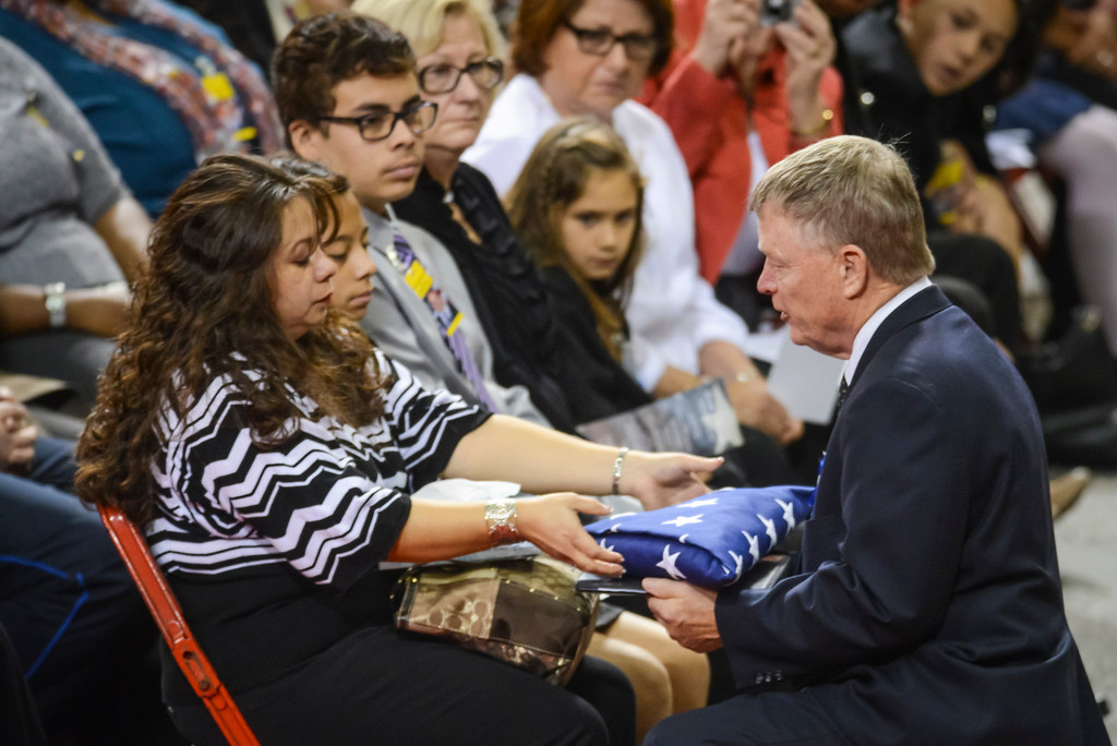 . Acting Secretary of U.S. Homeland Security, Ran Beers presents a flag to Ana Hernandez, wife of slain TSA officer Gerardo Hernandez at the Los Angeles Sports Arena Tuesday, November 12, 2013.  A public memorial was held for Officer Gerardo who was killed at LAX when a gunman entered terminal 3 and opened fire with a semi-automatic rifle.  ( Photo by David Crane/Los Angeles Daily News )
