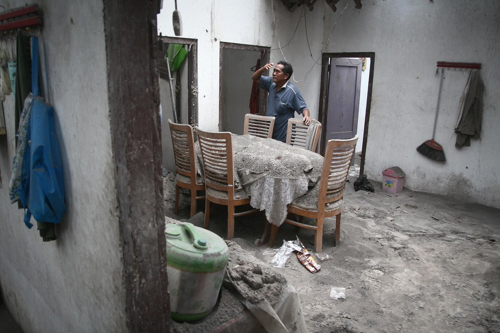 . A resident inspects his house damaged by heavy ashfall in Malang, East Java on February 16, 2014 following the volcanic eruption of Mount Kelud in East Java on February 13. Three Indonesian airports reopened February 15 while four others remained closed, officials said, after a volcanic eruption killed four people and forced mass evacuations. AFP PHOTO / Aman ROCHMAN/AFP/Getty Images