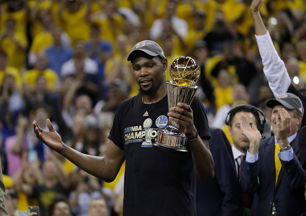 . Golden State Warriors forward Kevin Durant gestures as he holds the Bill Russell NBA Finals Most Valuable Player Award after Game 5 of basketball\'s NBA Finals between the Warriors and the Cleveland Cavaliers in Oakland, Calif., Monday, June 12, 2017. The Warriors won 129-120 to win the NBA championship. (AP Photo/Marcio Jose Sanchez)