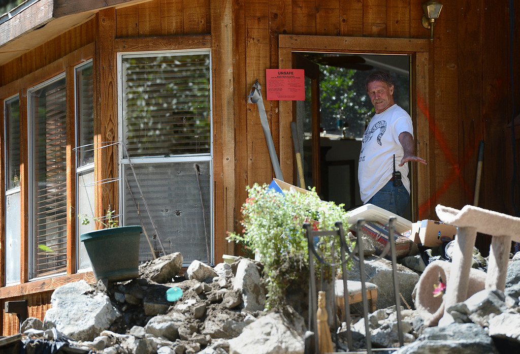 . Eric Olson stands in the doorway of his red-tagged home while trying to clean-up from Sunday\'s storm in Mt. Baldy, CA, Tuesday, August 5, 2014. (Photo by Jennifer Cappuccio Maher/Inland Valley Daily Bulletin)
