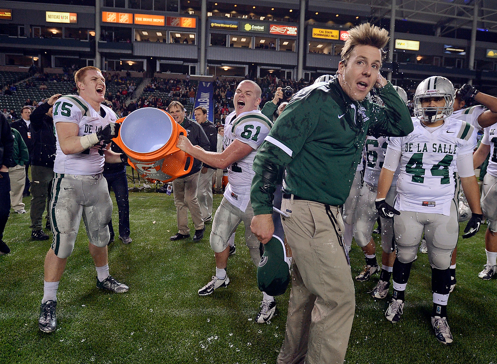 . De La Salle Spartans\' assistant coach Justin Alumbaugh wipes the water off his head after being doused by his players after defeating the Centennial Huskies in the Open Division during the 2012 CIF State Football Championship at Home Depot Center in Carson , Calif. on Saturday, Dec. 15, 2012. De La Salle defeated Centennial 48-28. (Jose Carlos Fajardo/Staff)