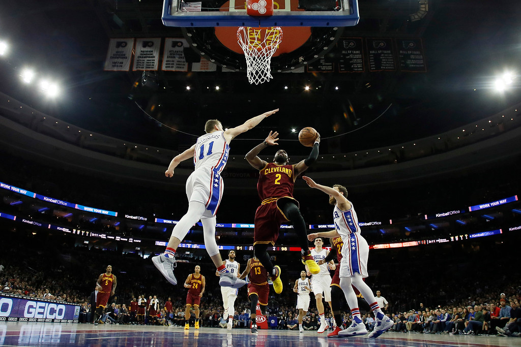 . Cleveland Cavaliers\' Kyrie Irving (2) goes up to shoot between Philadelphia 76ers\' Nik Stauskas (11) and Sergio Rodriguez (14) during the second half of an NBA basketball game, Sunday, Nov. 27, 2016, in Philadelphia. (AP Photo/Matt Slocum)