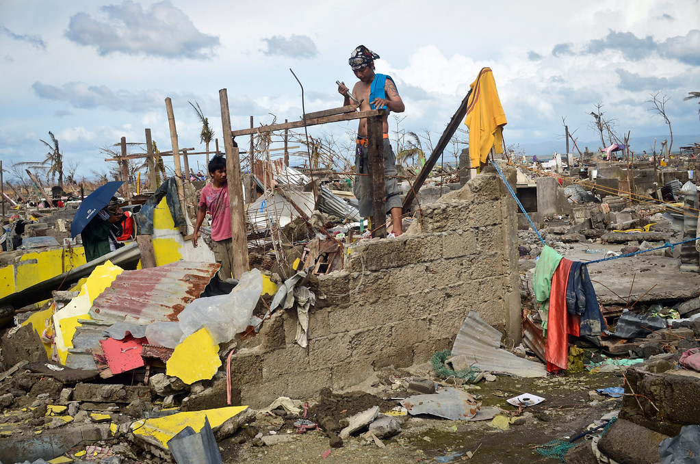 . A family tries to rebuild their shanty near the shoreline following the recent super typhoon on November 21, 2013 in Tacloban, Leyte, Philippines.  (Photo by Dondi Tawatao/Getty Images)