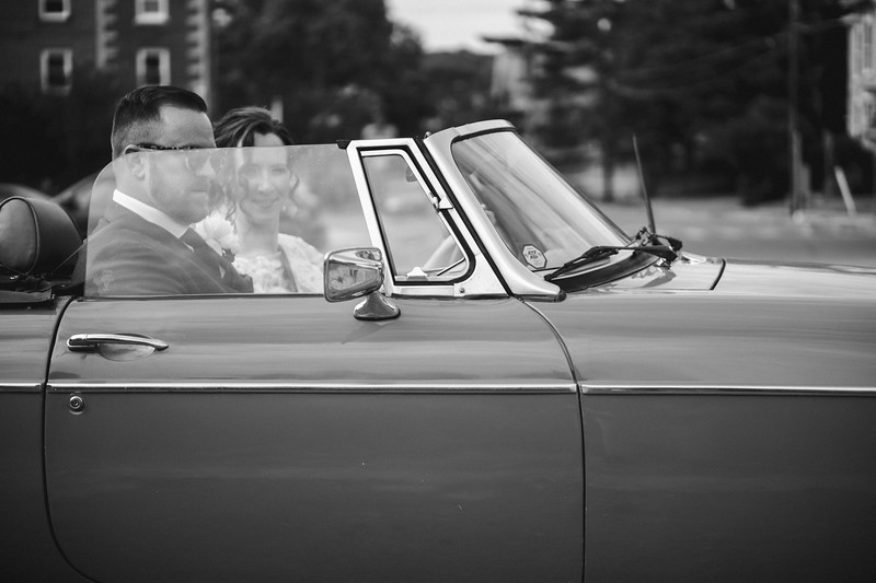 The bride smiles from inside of the convertible as they get ready to drive away.