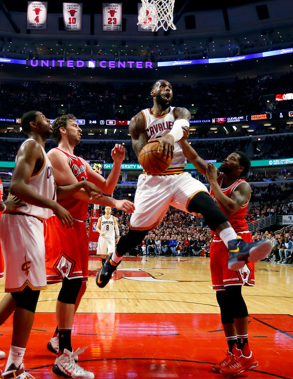 . Cleveland Cavaliers forward LeBron James, center, goes between Chicago Bulls center Pau Gasol, left and guard Aaron Brooks, right, during the second half of an NBA basketball game in Chicago, on Saturday, April 9, 2016. (AP Photo/Jeff Haynes)