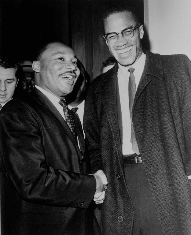 . Rev. Martin Luther King Jr., left, of the Southern Christian Leadership Conference, and Malcolm X smile for photographers in Washington March 26, 1964. They shook hands after King announced plans for direct action protests if Southern senators filibuster against civil rights bill. Malcolm, who has broken with the Black Muslims, predicted another march on Washington if a filibuster against the civil rights bill drags on. (AP Photo/Henry Griffin)