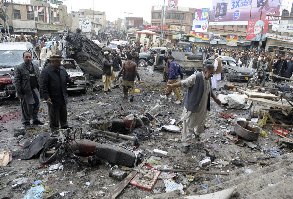 Description of . Bystanders are pictured at the site of a bomb explosion in Quetta on January 10, 2013. A bomb attack killed 11 people and wounded dozens more in a crowded part of Pakistan's southwestern city of Quetta, police said. AFP PHOTO/Banaras  KHAN/AFP/Getty Images