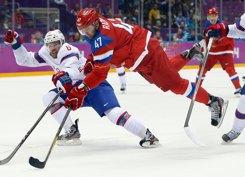 . Russia forward Alexander Radulov makes an off-balance shot against Norway defenseman Jonas Holos in the second period of a men\'s ice hockey game at the 2014 Winter Olympics, Tuesday, Feb. 18, 2014, in Sochi, Russia. (AP Photo/Mark Humphrey)