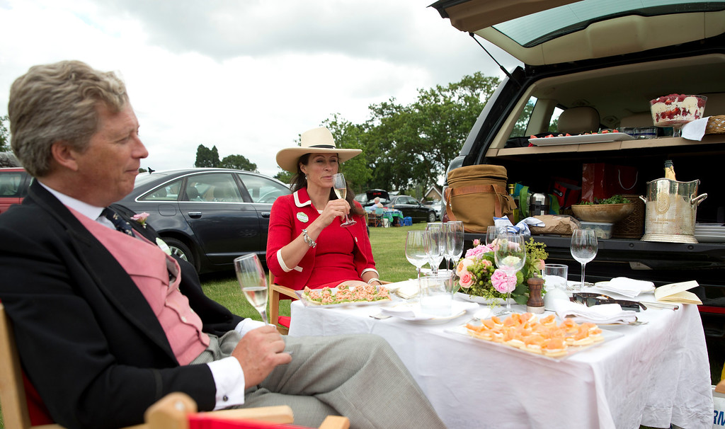. Simon Holland and his wife Lucy wait for his guests to arrive for a picnic in a car park on the second day of the Royal Ascot horse racing meeting at Ascot, England, Wednesday, June, 18, 2014.  (AP Photo/Alastair Grant)