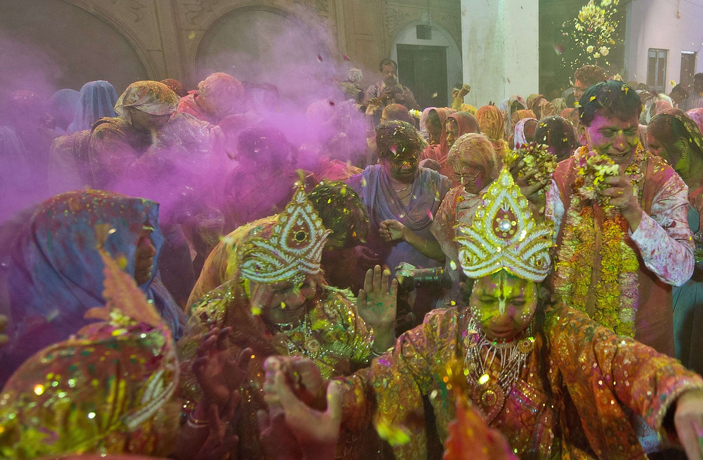 . Indian widows dressed as Hindu god Lord Krishna and Radha dance as Sulabh International founder Bindeshwari Pathak (R) sprinkles flower petals during Holi celebrations  in Vrindavan on March 14, 2014.  AFP PHOTO/Prakash SINGH/AFP/Getty Images