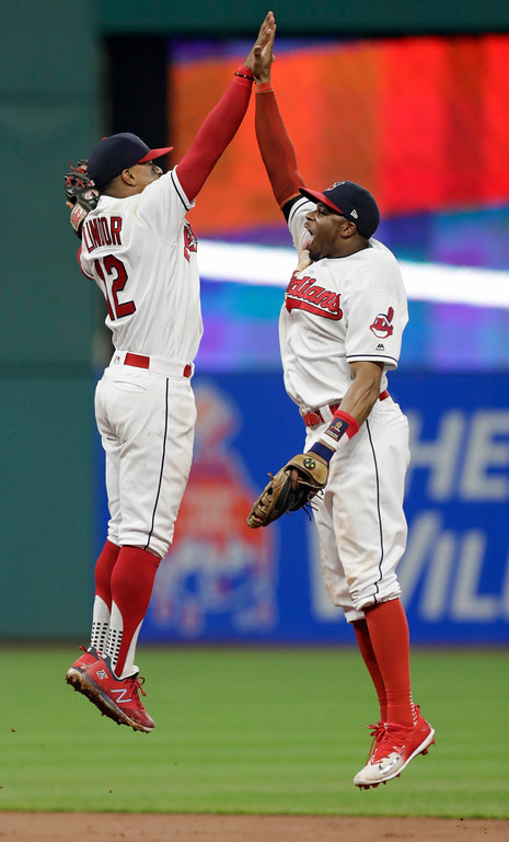 . Cleveland Indians\' Francisco Lindor, left, celebrates with Rajai Davis after the Indians defeated the Chicago White Sox 6-2 in a baseball game, Monday, June 18, 2018, in Cleveland. (AP Photo/Tony Dejak)
