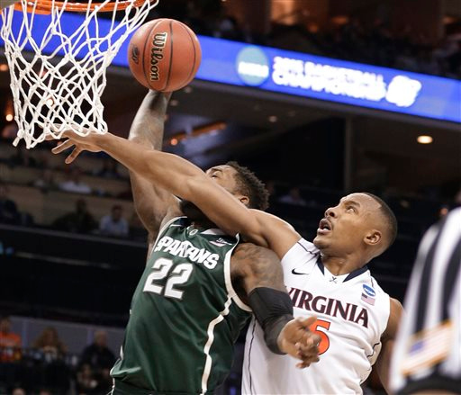 . Michigan State\'s Branden Dawson (22) is fouled by Virginia\'s Darion Atkins (5) during the second half of an NCAA tournament college basketball game in the Round of 32 in Charlotte, N.C., Sunday, March 22, 2015. (AP Photo/Nell Redmond)