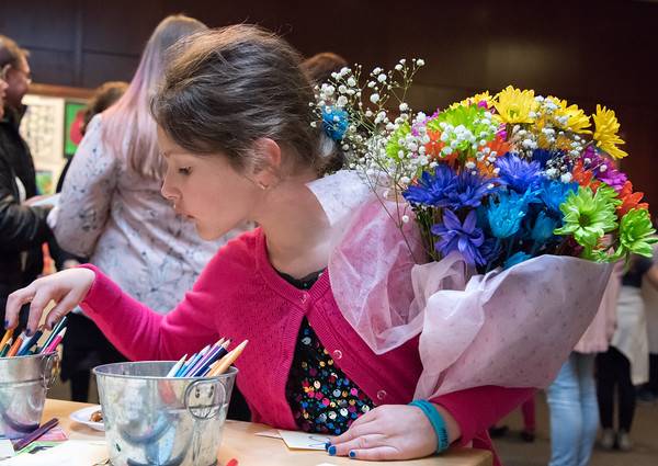 04/17/18 Wesley Bunnell | Staff Maya Miller, age 7 holds a bouquet of flowers she received from her mother Kathy Miller while looking through colored pencils to create artists cards. Original art work created by Berlin Public School students was on display during an opening reception held Tuesday night at the New Britain Museum of American Art.