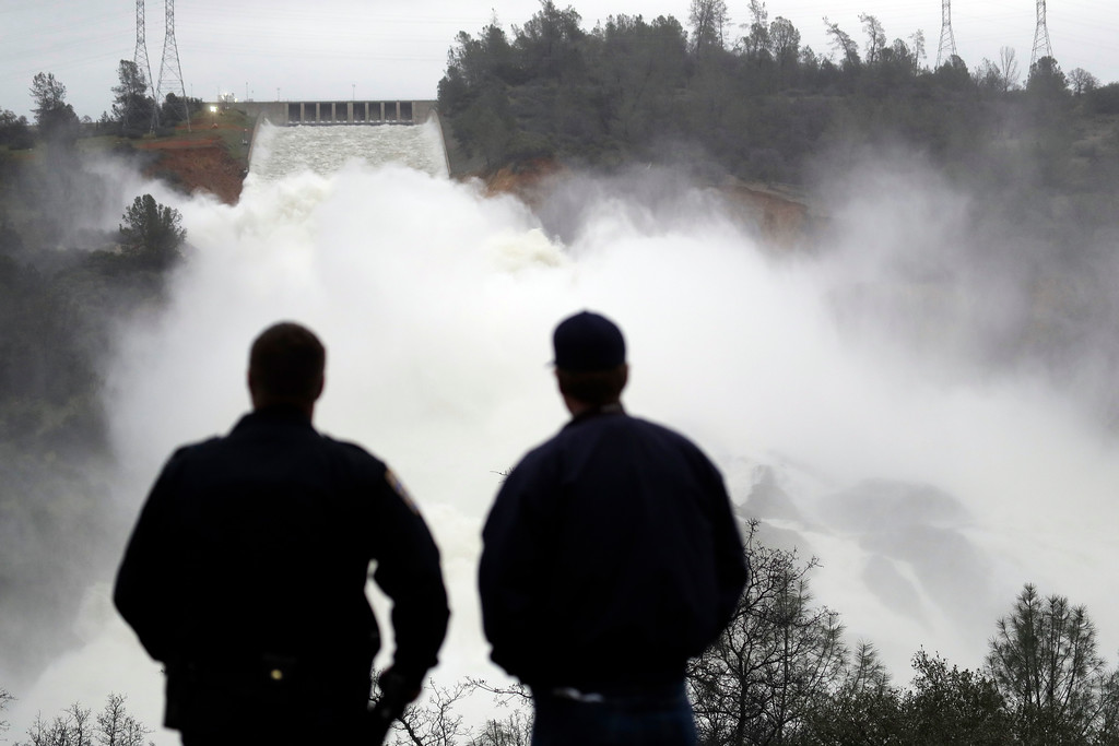 . Two men watch as water gushes from the Oroville Dam\'s main spillway Wednesday, Feb. 15, 2017, in Oroville, Calif. The Oroville Reservoir is continuing to drain Wednesday as state water officials scrambled to reduce the lake\'s level ahead of impending storms. (AP Photo/Marcio Jose Sanchez)