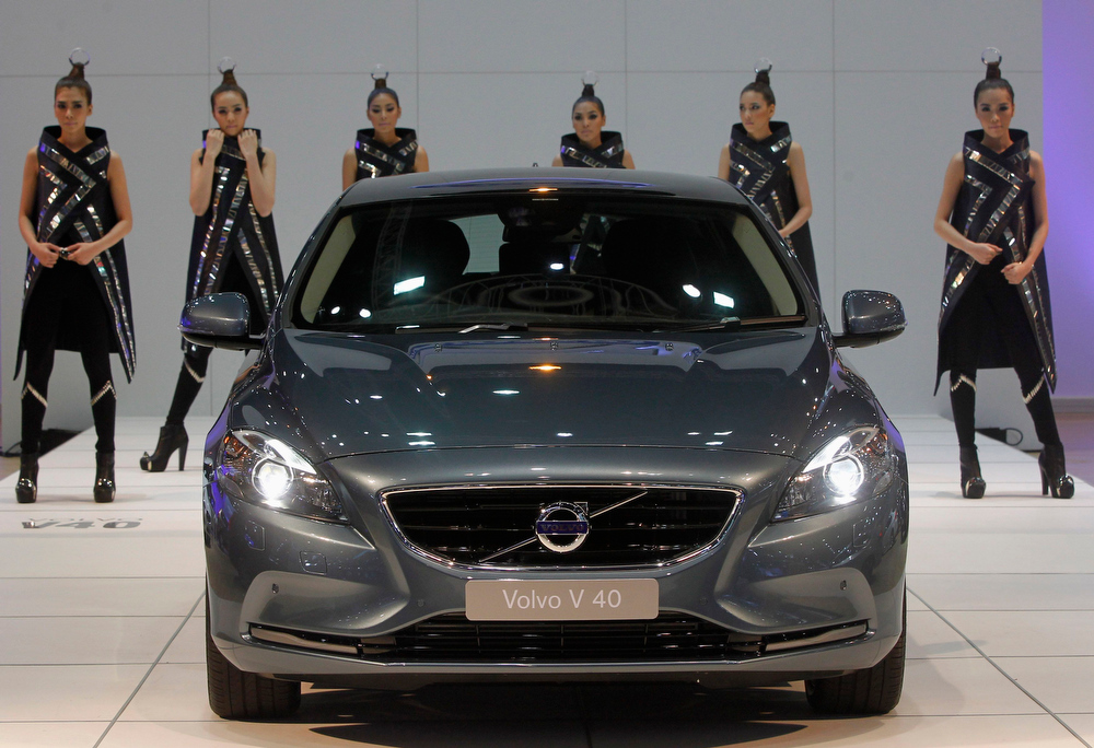 . Models pose behind a Volvo V 40 during a media presentation of the 34th Bangkok International Motor Show in Bangkok March 26, 2013. The Bangkok International Motor Show will be held from March 27 to April 7. REUTERS/Chaiwat Subprasom