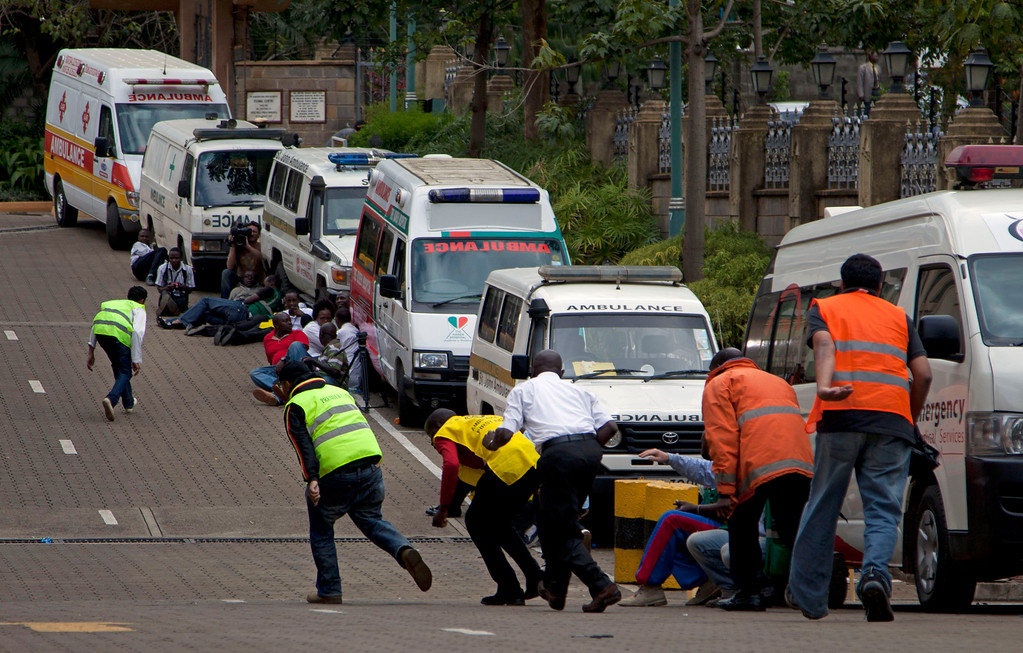 . Paramedics run beside parked ambulances outside the Westgate Mall in Nairobi after heavy shooting started for the third time since the morning Monday, Sept. 23, 2013. (AP Photo/Sayyid Azim)