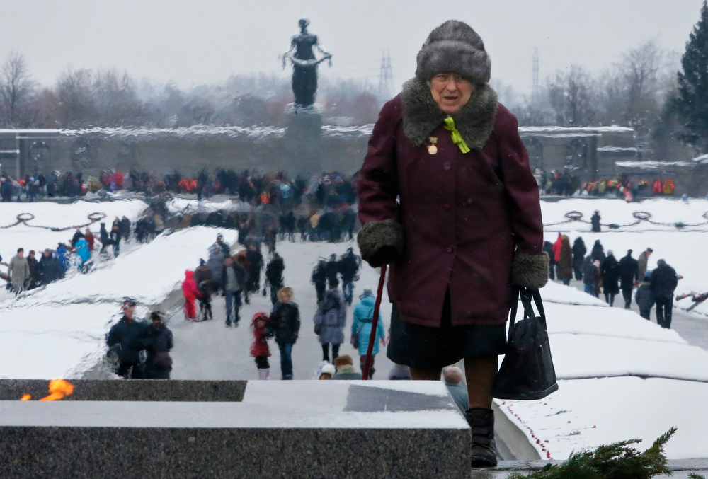 . Tamara Krylova, 82, who stayed in besieged Leningrad walks past an eternal flame at the Piskaryovskoye Cemetery where most of the Leningrad Siege victims were buried during World War II, in St.Petersburg, Russia, Sunday, Jan. 26, 2014. People gather to marked the 70th anniversary of the battle that lifted the Siege of Leningrad. The Nazi German and Finnish siege and blockade of Leningrad, now known as St. Petersburg, was broken on Jan. 18, 1943 but finally lifted Jan. 27, 1944. More than 1 million people died mainly from starvation during the 900-day siege. (AP Photo/Dmitry Lovetsky)