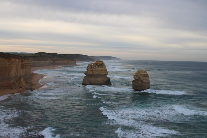 The reddish stone formation called the Apostles stands in the blue Southern Ocean on a Great Ocean Walk itinerary. The sky is streaked with clouds.