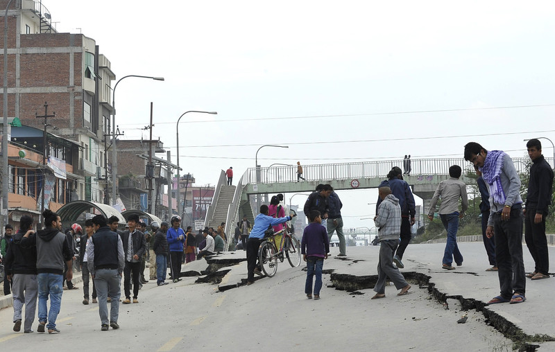 . Nepalese residents walk past road damage following an earthquake in Kathmandu on April 26, 2015. International aid groups and governments intensified efforts to get rescuers and supplies into earthquake-hit Nepal on April 26, 2015, but severed communications and landslides in the Himalayan nation posed formidable challenges to the relief effort. As the death toll surpassed 2,000, the US together with several European and Asian nations sent emergency crews to reinforce those scrambling to find survivors in the devastated capital Kathmandu and in rural areas cut off by blocked roads and patchy phone networks. PRAKASH MATHEMA/AFP/Getty Images