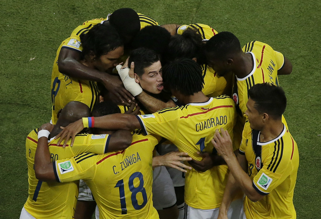 . Colombia\'s midfielder James Rodriguez (C) is mobbed by teammates as he celebrates scoring a goal during the Round of 16 football match between Colombia and Uruguay at The Maracana Stadium in Rio de Janeiro on June 28, 2014,during the 2014 FIFA World Cup. FELIPE DANA/AFP/Getty Images