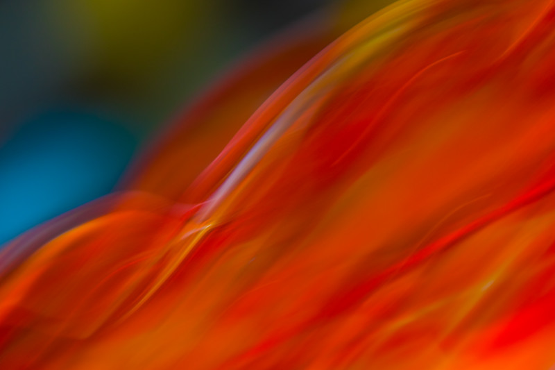 Deep red and orange waves of color waft across this abstract image that includes light green and blues.