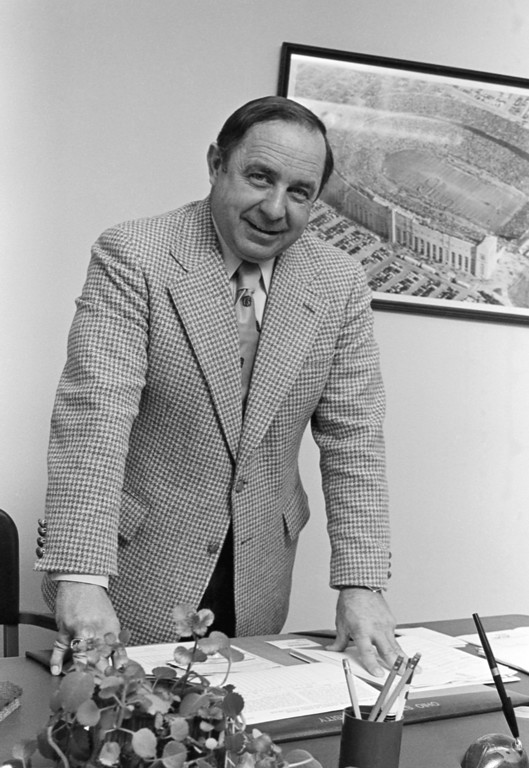 . Ohio State football coach Earle Bruce leans on the desk in his new office, posing before a photograph of Ohio stadium after he was named to replace the fired Woody Hayes in Columbus, Ohio, Jan. 13, 1979 . Bruce, 47, left the coaching job at Iowa to become the Buckeyes mentor. (AP Photo/Doug Martin)