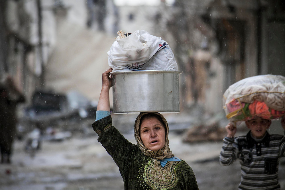 . In this Tuesday, Dec. 11, 2012 photo, a Syrian woman and girl carry their belongings after their home was damaged due to fighting between Free Syrian Army fighters and government forces in Aleppo, Syria. (AP Photo/Narciso Contreras)