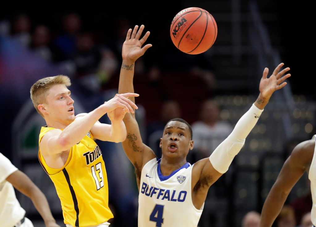 . Toledo\'s Jaelan Sanford, left, passes against Buffalo\'s Davonta Jordan during the first half of an NCAA college basketball championship game of the Mid-American Conference tournament, Saturday, March 10, 2018, in Cleveland. (AP Photo/Tony Dejak)