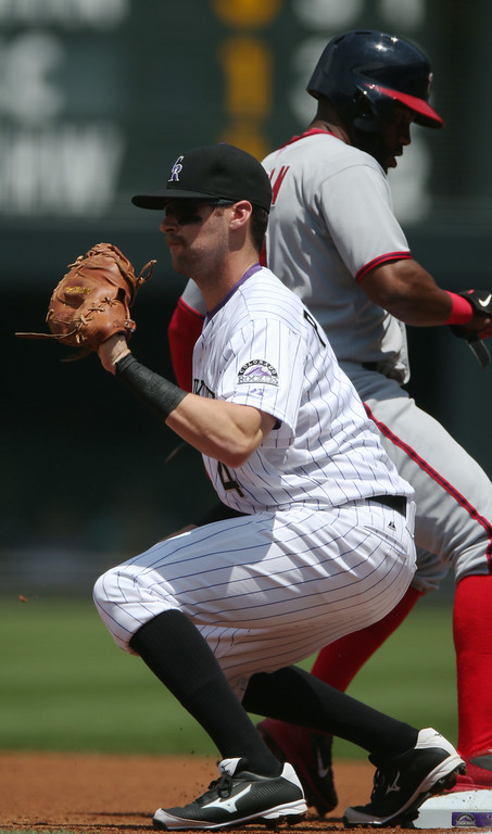 . Colorado Rockies first baseman Ben Paulsen, front, fields a pickoff throw as Washington Nationals\' Denard Span returns to first base in the first inning of a baseball game in Denver, Wednesday, July 23, 2014. (AP Photo)
