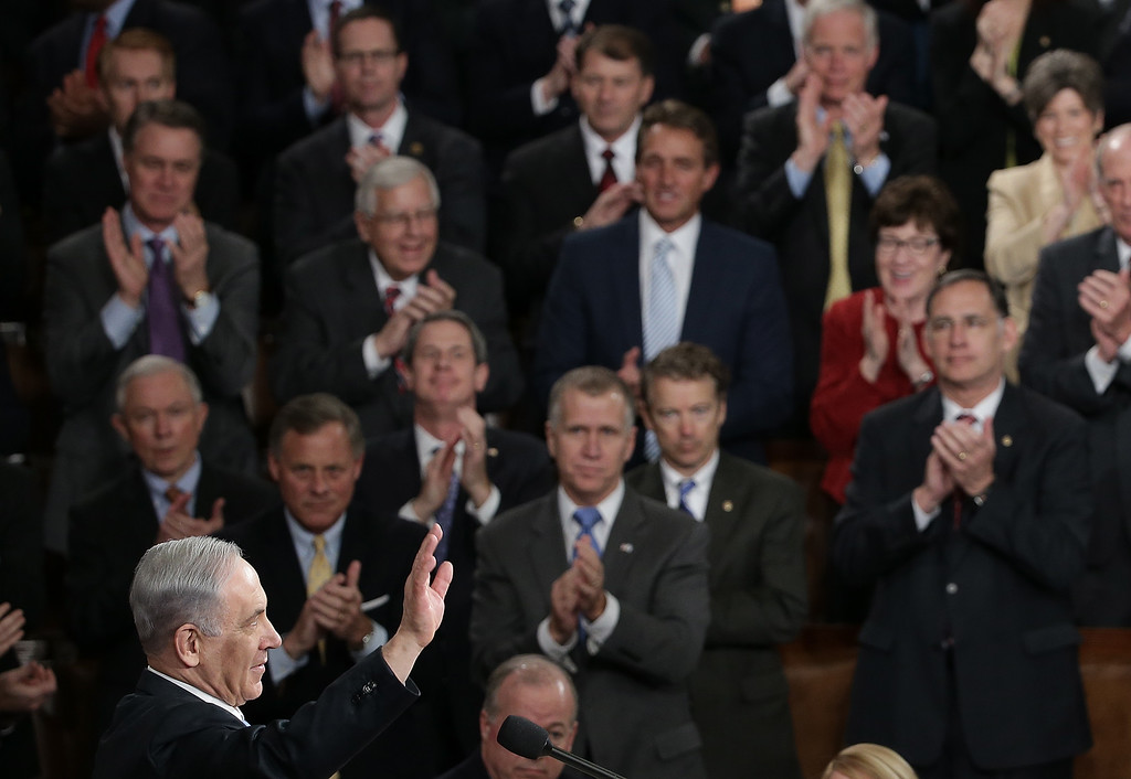 """. sraeli Prime Minister Benjamin Netanyahu acknowledges a standing ovation after addressing a joint meeting of the United States Congress in the House chamber at the U.S. Capitol March 3, 2015 in Washington, DC. During his speech, Netanyahu said, \""""Today the Jewish people face yet another attempt by another Persian potentate to destroy us.\""""  (Photo by Win McNamee/Getty Images)"""