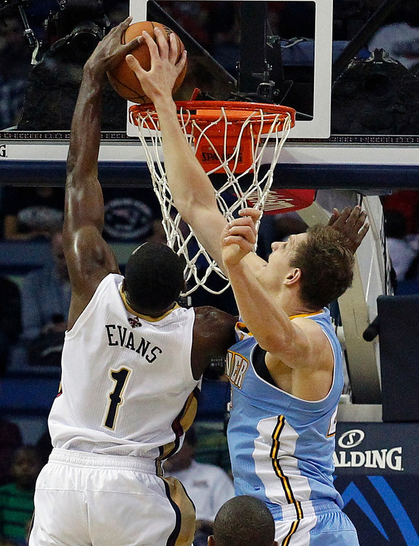 . New Orleans Pelicans small forward Tyreke Evans (1) goes to the basket as Denver Nuggets center Timofey Mozgov defends in the first half of an NBA basketball game in New Orleans, Sunday, March 9, 2014. (AP Photo/Bill Haber)