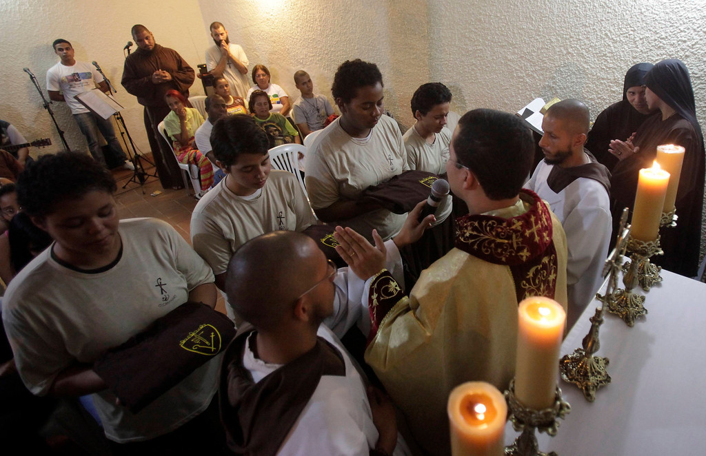 """. Members of Franciscan fraternity, O Caminho, (L-R)  Renata Florencio, Palloma Barradas, and Juliana Santos, receive their habits upon reaching the level of \""""aspirant\"""", during a mass at at the group\'s house in the Campo Grande neighbourhood of Rio de Janeiro, April 8, 2013. O Caminho (The Way) are a group of Franciscan monks and nuns who help the homeless on the streets of Rio de Janeiro. They consider the election of Pope Francis, the first pontiff to take the name of St Francis of Assisi, to be a confirmation of their beliefs in poverty and simplicity. In July, Pope Francis will visit Rio de Janeiro in his first international trip since assuming the papacy. Picture taken April 8, 2013. REUTERS/Ricardo Moraes"""